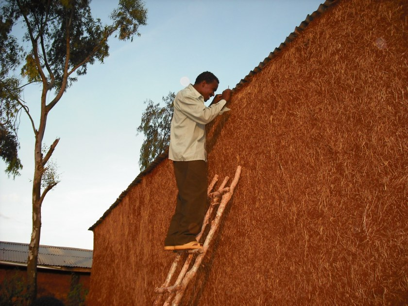 A Guji believer wiring electricity for the back of the home